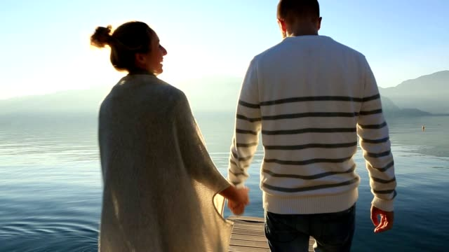 couple holding hands on wooden pier - piemonte video stock e b–roll