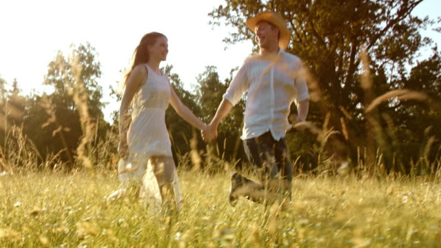 SLO MO TS Couple holding hands running across summer meadow