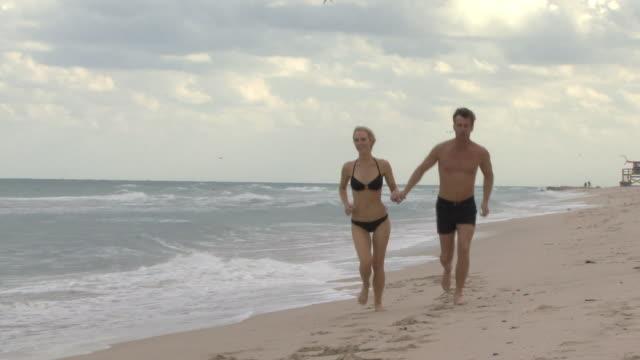 ws cu couple holding hands running on beach / miami, florida, usa - サーフパンツ点の映像素材/bロール