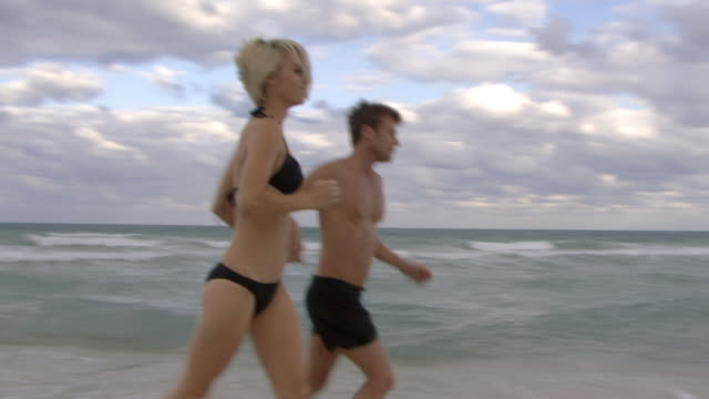 ms pan couple holding hands running on beach / miami, florida, usa - swimming shorts stock videos & royalty-free footage