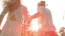 SLO MO Couple holding hands running towards sun