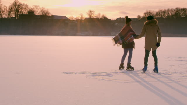 4K Couple holding hands skating on sunny frozen lake, slow motion