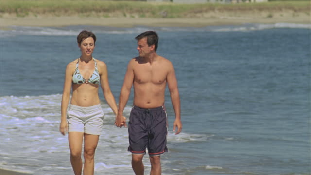 WS Couple holding hands, talking and walking along water's edge on beach / Phippsburg, Maine, USA