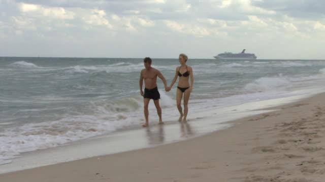 ws couple holding hands wading in ocean waves / miami, florida, usa - サーフパンツ点の映像素材/bロール