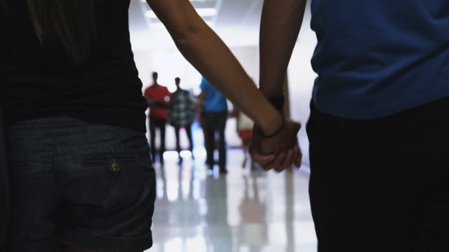 CU Couple holding hands walking down school corridor / Spanish Fork City, Utah, USA