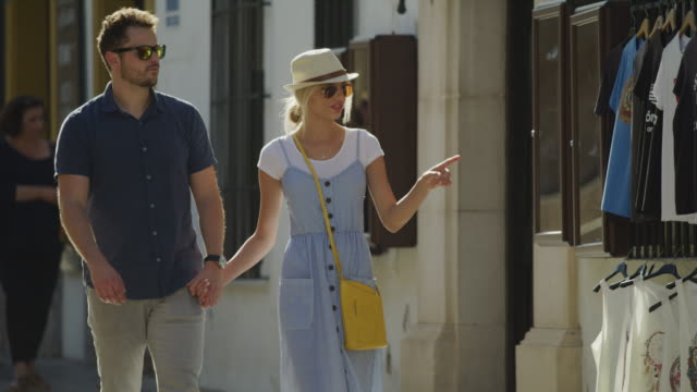 couple holding hands walking in city pausing at clothing store / cordoba, cordoba, spain - sonnenbrille stock-videos und b-roll-filmmaterial