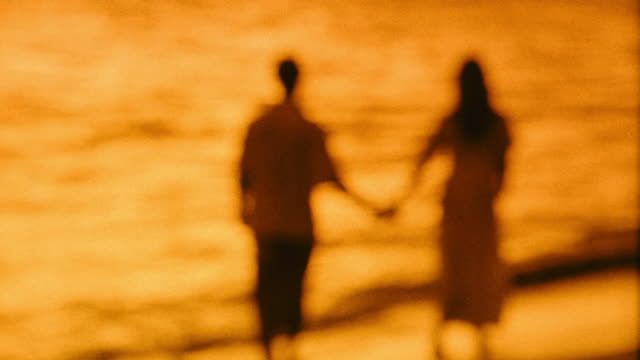 vídeos de stock e filmes b-roll de orange out-of-focus rear view couple holding hands walking on beach at sunset / hawaii - perto