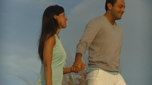 ms pan couple holding hands walking on beach dunes, eastville, virginia, usa - gemeinsam gehen stock-videos und b-roll-filmmaterial