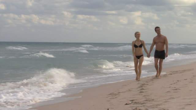 ws ms couple holding hands walking on beach / miami, florida, usa - swimming shorts stock videos & royalty-free footage