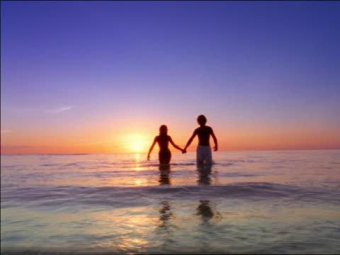 vídeos y material grabado en eventos de stock de couple holding hands walking out of water towards camera at sunset / seychelles - traje de baño de una pieza