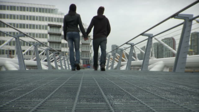WS SLO MO Couple holding hands walking through bridge / Vancouver, British Columbia, Canada