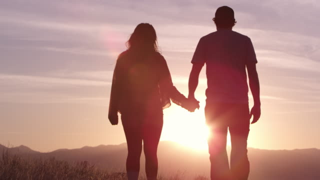 couple holding hands walking towards sunset as they kiss - halten stock-videos und b-roll-filmmaterial