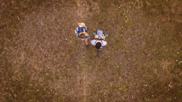 paare halten hände beim wandern auf dem feld - wandern stock-videos und b-roll-filmmaterial