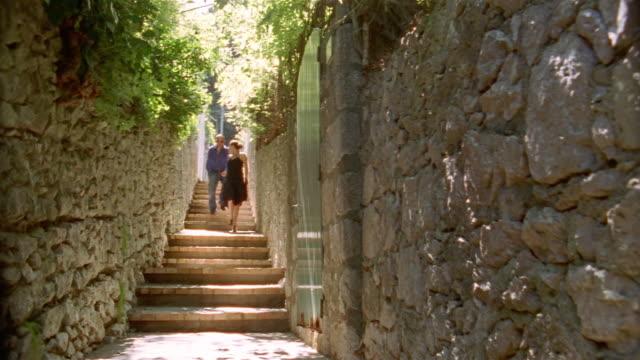 stockvideo's en b-roll-footage met couple holding hands while running down steps in alleyway / capri - zonnejurk