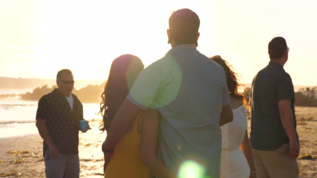 ms couple holding hands while walking on beach with family at sunset - pacific islander family stock videos & royalty-free footage