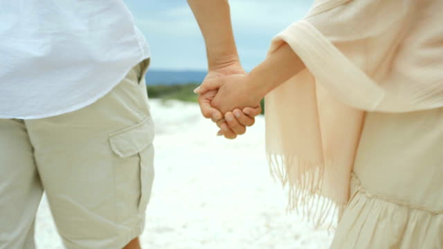 Couple holding hands while walking on the beach