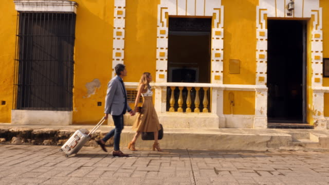 ms td couple holding hands while walking through town with luggage on way to boutique hotel - america latina video stock e b–roll