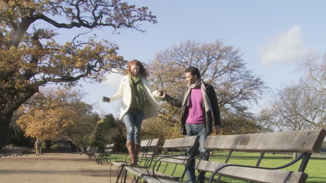 Couple holding hands, woman walking across benches