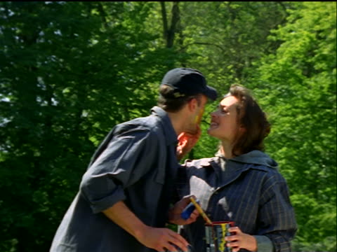 vidéos et rushes de couple holding paint brushes hugging + kissing + woman putting paint on man's face outdoors - casquette de baseball