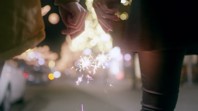 WS Couple holding sparklers while walking in the city at Christmas time