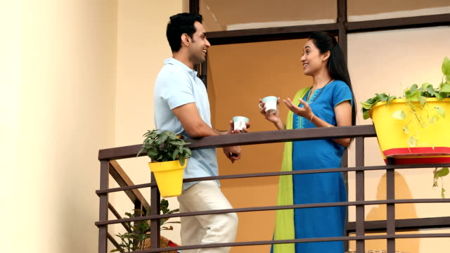 ms couple holding tea cup and talking in balcony / sonipat, haryana, india - haryana stock-videos und b-roll-filmmaterial