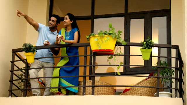 ms pan couple holding tea cup and talking with each other in balcony / sonipat, haryana, india - haryana stock-videos und b-roll-filmmaterial