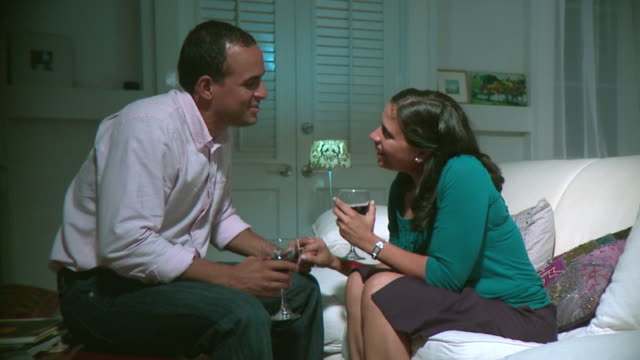 MS PAN Couple holding wine glasses embracing in living room, Panama City, Panama