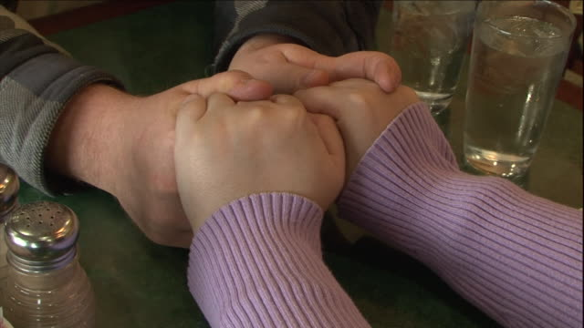 a couple holds hands across a table. - holding hands stock videos & royalty-free footage