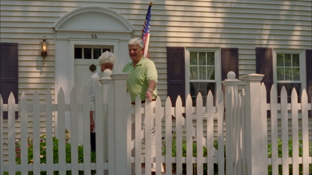 a couple holds hands as they walk through the gate of a picket fence. - picket fence stock videos and b-roll footage