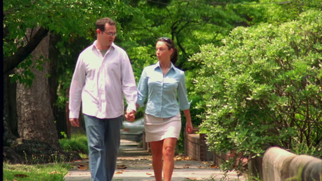 A couple holds hands walking down a tree lined sidewalk.