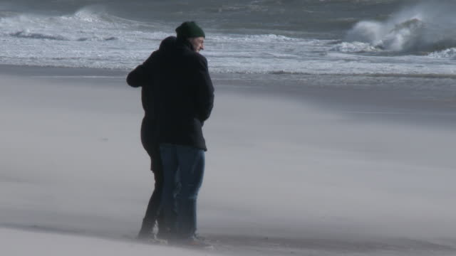 A couple holds on to each other tightly along the shoreline at Jones Beach New York as powerful gale force winds sand blast them