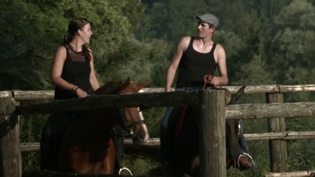 couple horseback riding on ranch - medium shot stock-videos und b-roll-filmmaterial