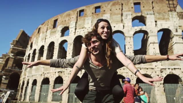 vidéos et rushes de couple hug en face du coliseum - rome