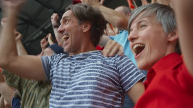 couple hugging and celebrating the score of their team on the stadium tribune - audience video stock e b–roll