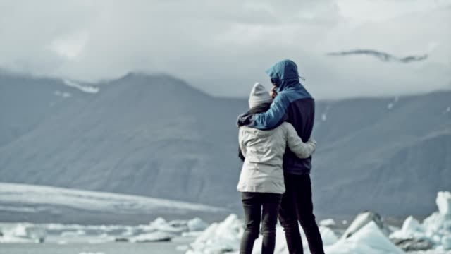 couple hugging and looking at glacier lagoon - glacier stock videos & royalty-free footage