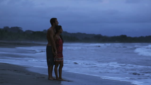 couple hugging and standing on the beach - 恋に落ちる点の映像素材/bロール