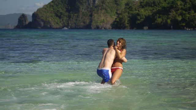 couple hugging and walking in the shallow water - shorts stock videos & royalty-free footage