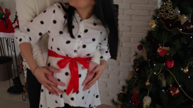 couple hugging by the christmas tree - tree hugging stock videos & royalty-free footage