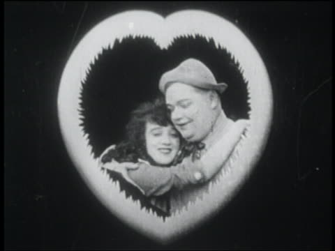 b/w 1916 couple (fatty arbuckle + mabel normand) hugging framed by heart - falling in love stock videos and b-roll footage