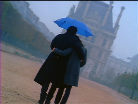 canted rear view couple hugging + holding blue umbrella while walking towards building / paris - paar mittleren alters stock-videos und b-roll-filmmaterial