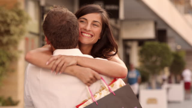 Couple hugging in street with shopping bags