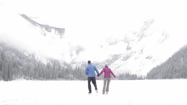 Couple ice skating, holding hands on a frozen mountain lake in Glacier Park, Montana