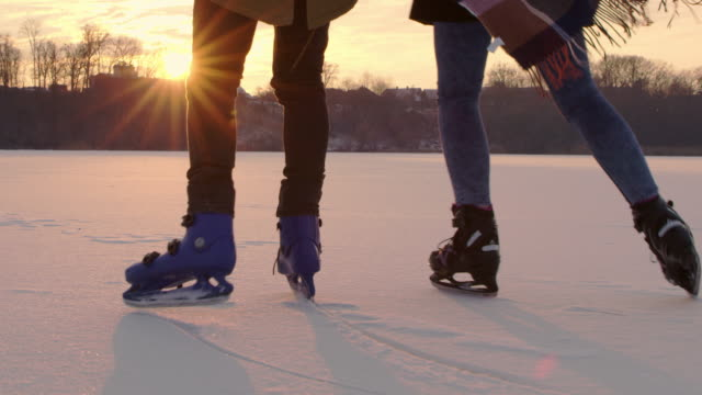 4k couple ice skating on frozen lake, slow motion - ice skating stock videos & royalty-free footage