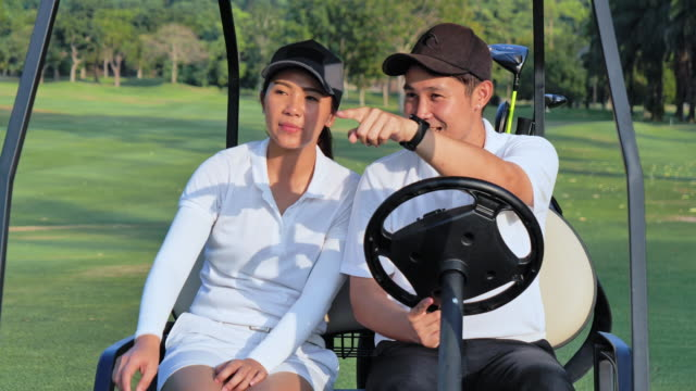 couple in a golf cart at the golf course. - green golf course stock videos & royalty-free footage
