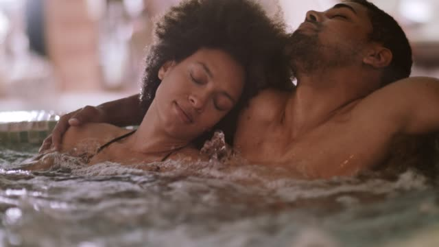 vídeos de stock e filmes b-roll de couple in a hot tub - spa