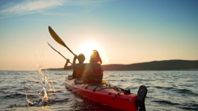 slo mo couple in a red sea kayak passing by on the water in sunshine - kayaking stock videos & royalty-free footage