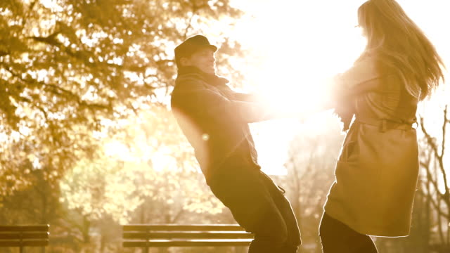 couple in a romantic attitude in a park during autumn - sepia stock videos and b-roll footage