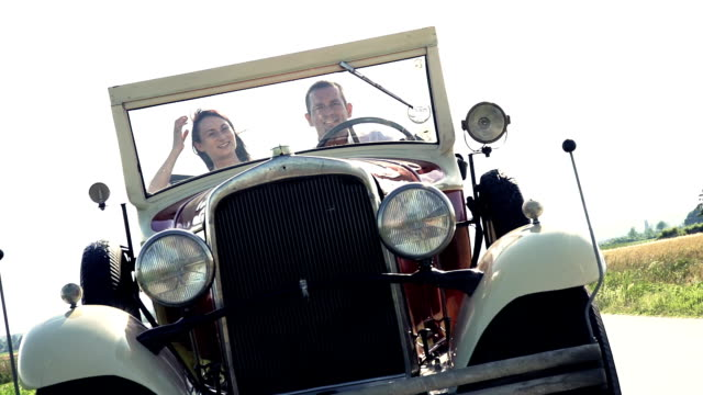 hd super slow-motion: couple in a vintage convertible car - horseless carriage stock videos & royalty-free footage