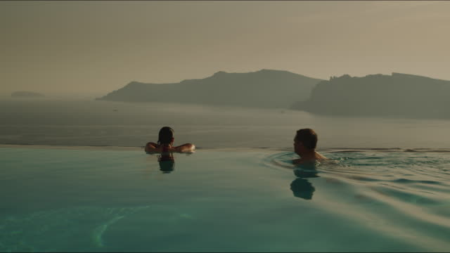 couple in an infinity pool - oia santorini stock videos & royalty-free footage