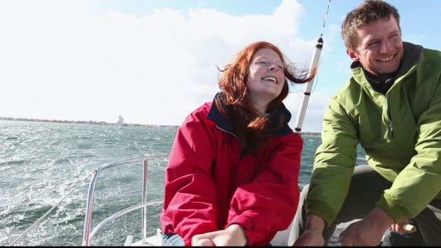 MS Couple in back of sailing yacht turning crank and laughing / Copenhagen, Denmark